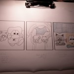 A photograph of Friday's episode of The Life of Nob T. Mouse, showing crayon colours in two panels and inking in all three panels.