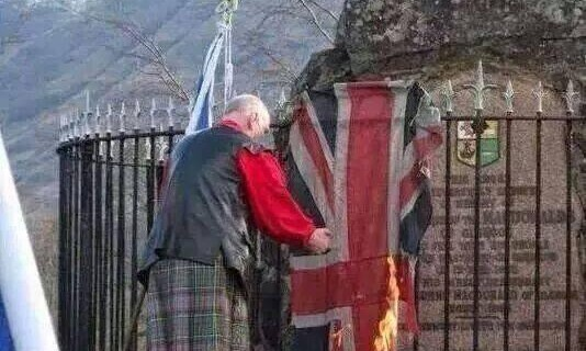 Scottish Nationalist burns the Union Flag beside a war memorial. Image via @LordSkipVC